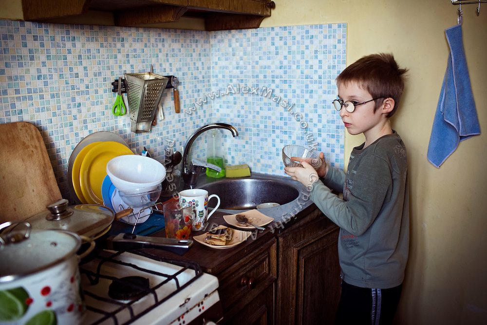 Yaroslav, 10, is washing dishes in the kitchen of the provisional home where he resides with his mother Olga, 36, as internally displaced persons. (IDPs) Yeroslav is taking part to the UNICEF-sponsored One Minute Junior project for internally displaced persons (IDPs), carried out by the local NGO 'Ukrainian Frontiers' in the city of Kharkiv, the country's second-largest, in the east. The conflict between Ukrainian army and Russia-backed separatists nearby, in the Donbass region, have left more than 10000 dead since April 2014, including over 1000 since the shaky Minsk II ceasefire came into effect in February 2015. The approximate number of people displaced by the conflict is 1.4 million as of August 2015. Yeroslav's mother, Olga, is also a participant to a different project of 'Ukrainian Frontiers', called 'Self-Employment', first as a beneficiary, and now as a paid hotline coordinator for people seeking jobs and formation courses.