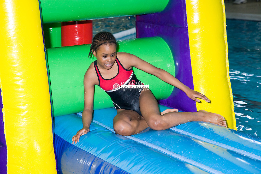 Girl playing on an inflatable float in the swimming in the pool at her local leisure centre,