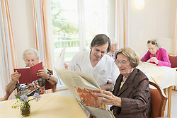 Caregiver reading newspaper with senior woman in rest home, Bavaria, Germany