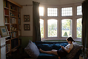 A young woman reads messages on her phone while lying on her sofa by the front bay window of a house in south London, 20th August 2020, in London, England.