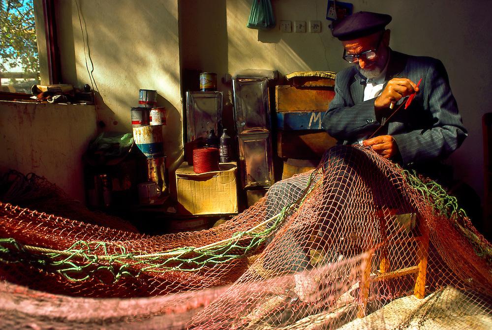 Turkish fisherman repairing fishing net, Anadolukavagi (on the Bosporus Straight, near the Black Sea), Turkey