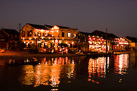Colourful lights reflect in the Thu Bon river along Hoi An's waterfront at night.