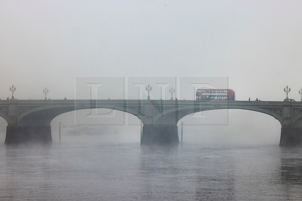 © Licensed to London News Pictures. 05/11/2020. London, UK. A red London bus crosses a foggy River Thames on Westminster Bridge in central London on the first day of England's national lockdown. Photo credit: London News Pictures