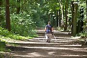 Nederland, Berg en Dal, 7-6-2015Een vrouw ( van de fotograaf) loopt in het bos met Nordic Walking stokken. Nordicwalkingstokken, nordicwalking, walkingstokken