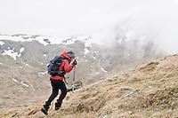 Female hiker ascends grassy mountain slope in Scottish highlands