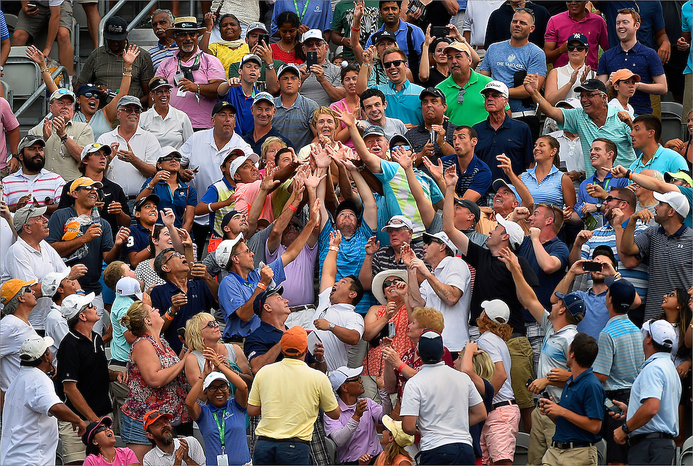 Spectators fight for the ball thrown by Jason Day (not pictured) during the final round of The Barclays Championship held at Plainfield Country Club in Edison, New Jersey on August 30.