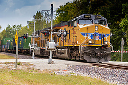 Union Pacific Engine 2662  a GE AC44CWCTE, pulls a line of flats carrying containers and trailers through a crossing at Funks Grove Illinois just west of Historic US Route 66, The Mother Road