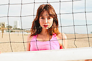 A portrait of a young woman in front of volleyball net.