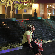 Charlotte, NC- September 22, 2016: Jessica Smith (left) and Michaela McCormick (right) sit outside Bank of America Headquarters as Naional Guard members stand post behind them.  CREDIT: LOGAN R. CYRUS FOR THE NEW YORK TIMES