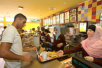 07 Sep 2005, Clichy-sous-Bois, France --- The name Beurger King Muslim is a play on the slang word Beur, or North Africans.  It is a fast food place serving only Halal meats, found in Clichy-sous-Bois, a northern suburb of Paris populated mostly by first or second generation immigrants from the former French colonies of North Africa and Africa. --- Image by © Owen Franken/Corbis