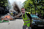 A protester wearing a Macron mask that say: associate of the devil.