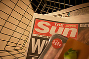 "The Sun newspaper in a shopping basket in London, England, UK. British police arrested five senior members of staff at News Corporation's newspaper The Sun, as part of investigations into alleged payments to police by journalists for information. This story continues the controversy surrounding News International with regards to the phone hacking scandal. Trevor Kavanagh, the newspapers's associate editor said the senior members of staff had been treated like ""an organised gang"" and the tabloid was ""not a swamp that needed draining"". He said money sometimes changed hands while unearthing stories, and this had always been standard practice. The Met Police declined to comment."