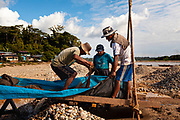 Miners wash and shake a carpet to separate the gold sediments on a riverbed, near to Boca Colorado, Peru.