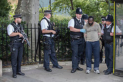 © Licensed to London News Pictures. 22/06/2017. London, UK. Armed police (L) stand guard as colleagues detain a man who earlier was tasered near an entrance to Parliament. Photo credit: Peter Macdiarmid/LNP