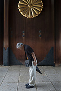 An older Japanese man bows as he enters the shrine under gate with the Imperial Chrysanthemum crest on the door as Yasukuni shrine marks the 72nd anniversary of the end of the Pacific War. Yasukuni Shrine, Kudanshita, Tokyo Japan. Tuesday August 15th 2017. Nominally a event to honour Japan's war dead and call for continued peace, this annual gathering  at Tokyo's controversial Yasukuni  Shine also allows many Japanese nationalists to display their nostalgia for their Imperial past.Rightwing paramilitary groups, Imperial cos-players, politicians and many ordinary citizens come together at the shrine to march and wave flags. The day goes almost unreported in the mainstream Japanese media.