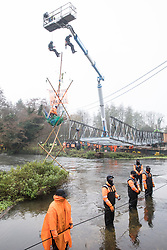 Denham, UK. 8th December, 2020. Bailiffs abseil from a large cherry picker towards Dan Hooper, widely known as Swampy during the 1990s, who is sitting on a bamboo tripod positioned in the river Colne. The climate and roads activist had occupied the tripod the previous day in order to delay the building of a bridge as part of works for the controversial HS2 high-speed rail link and a large security operation involving officers from at least three police forces, the National Eviction Team and HS2 security guards was put in place to facilitate his removal.