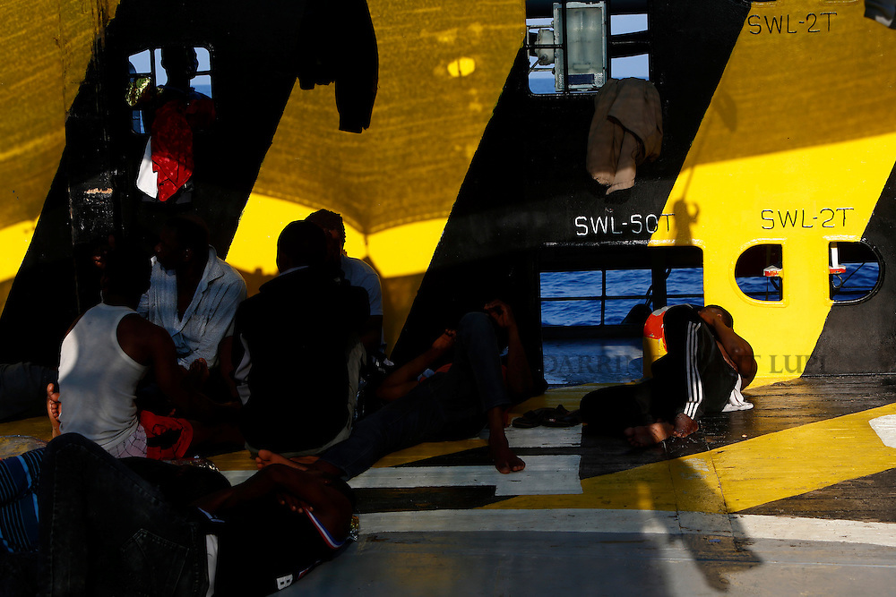 Migrants rest on the deck of the Medecins san Frontiere (MSF) rescue ship Bourbon Argos somewhere between Libya and Sicily August 8, 2015.  Some 241 mostly West African migrants on the ship are expected to arrive on the Italian island of Sicily on Sunday morning, according to MSF.<br /> REUTERS/Darrin Zammit Lupi <br /> MALTA OUT. NO COMMERCIAL OR EDITORIAL SALES IN MALTA