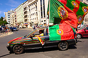 Portuguese supporter celebrating with national flags in his decorated car in a street in Lisbon. Portugal's national squad won the Euro Cup the day before, beating in the final France, the organizing country of the European Football Championship, in a match that ended 1-0 after extra-time.