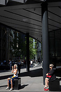 Women sit in a small area of sunlight on Fenchurch Avenue in the City of London - the capitals financial district, on 6th June 2018, in London, England.
