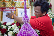 Apr. 15, 2010 - BANGKOK, THAILAND:  A man touches the photo of his son, who died in street fighting Saturday, during a chanting service at Wat Hualamphong in central Bangkok Thursday for the people who died during anti-government street violence Saturday. Another protestor died today, bringing the civilian death toll to 17. Hundreds of people are still hospitalized and many are in intensive care. Officials expect the death toll to increase through the week as people die of their wounds. A date has not been set for the victims' Buddhist funeral rites, but the chanting services will continue on a daily basis until the dead are cremated. Many people believe a violent government crackdown is less likely now since the violence seems to have shocked many Thais, but it has also galvanized protestors who show no sign of backing down.   Photo By Jack Kurtz