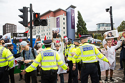 London, UK. 2 September, 2019. Police officers remove from the road outside ExCel London activists holding images of Palestinian children killed by Israeli attacks on Gaza on the first day of week-long protests against DSEI 2019, the world's largest arms fair. The first day of creative action was hosted by activists calling for a ban on arms exports to Israel and featured workshops, speakers, street theatre and dance. Israeli arms companies display weapons at DSEI marketed as 'combat-proven' following deployment against Palestinian communities.