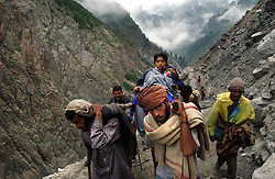 KASHMIR,INDIA, AUGUST 3:Enveloped by the rugged and picturesque Himalayan mountains, a Hindu woman and her child are carried by  palanquin bearers (chairs carried on poles by two or four people) as they make their pilgrimage to the holy cave of Amarnath, one of the most revered of Hindu shrines, near Baltal, about 70 miles northeast of Srinagar, August 3, 2003.    21,000 paramilitary soldiers and policemen have been deployed along the mountain route to protect the pilgrims from Islamic guerrillas, who have been fighting for independence of the Indian-controlled portion of Kashmir since 1989.