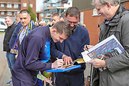 AFC Wimbledon defender Steve Seddon (15) signing autographs whilst holding a mango during the EFL Sky Bet League 1 match between AFC Wimbledon and Gillingham at the Cherry Red Records Stadium, Kingston, England on 23 March 2019.