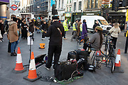 Buskers playing amplified guitar and drums outside Tottenham Court Road tube station on 21st January 2020 in London, England, United Kingdom. Over recent years there have been increasing complaints about the amplification used by some buskers, which is seen an excessive noise pollution, especially for people working nearby.