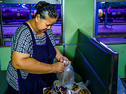 31 MAY 2017 - CHACHOENGSAO, THAILAND:  A vendor puts together meals for passengers on a Bangkok bound train at the train station in Chachoengsao, a provincial town about 50 miles and about an hour by train from Bangkok. The train from Chachoengsao to Bangkok takes a little over an hour but traffic on the roads is so bad that the same drive can take two to three hours. Thousands of Thais live outside of Bangkok and commute into the city for work on trains, busses and boats.      PHOTO BY JACK KURTZ