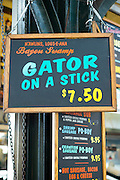 Sign offers Gator on a Stick at cafe bar in French Market food market on Decatur Street, French Quarter of New Orleans, USA