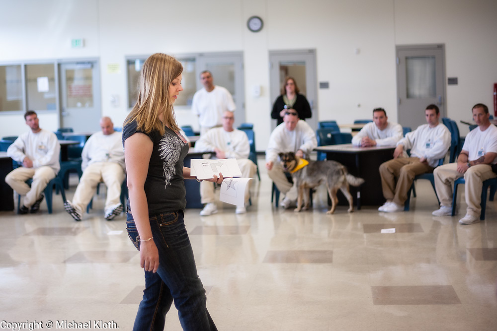 In this photo, Ms. E. demonstrates how the dog handlers will work with their dog through a Rally-O course.
