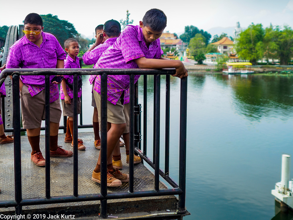 "09 JANUARY 2019 - KANCHANABURI, THAILAND: Thai students on a school field trip walk across the ""Bridge On the River Kwai"" in Kanchanaburi. Hundreds of thousands of Asian slave laborers and Allied prisoners of war died in World War II constructing the ""Death Railway"" between Bangkok and Rangoon (now Yangon), Burma (now Myanmar) for the Japanese during World War II.  The bridge is now one of the most famous tourist attractions in Thailand.      PHOTO BY JACK KURTZ"