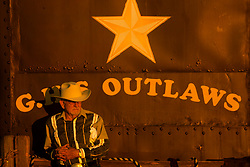 older cowboy standing in front of a painted sign