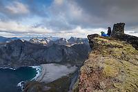 Two hikers take in view over Bunes beach from summit of Storskiva mountain peak, Lofoten Islands, Norway