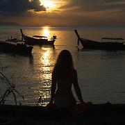 Silhouette of a girl sitting on a fallen tree on the beach, Ko Lipe, Thailand
