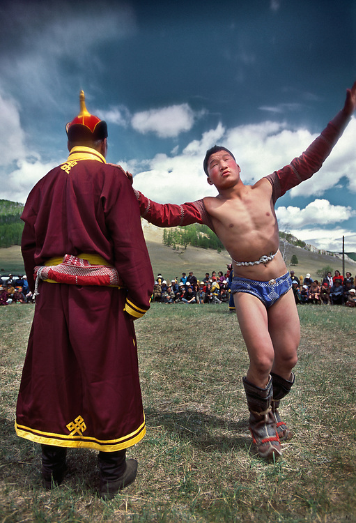 """Mongolian wrestling (Mongolian: bökh) is a traditional sport that has existed in Mongolia for centuries.<br /> Wrestling is one of Mongolia's age-old """"Three Manly Skills"""" (along with horsemanship and archery).<br /> The wrestler, dressed in an open-chested wrestling shirt, called a zodog, is performing a traditional dance before a match. He keeps one hand on his trainer's shoulder and circles around him a few times, keeping his eyes closed most of the time."""