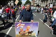 Political artist Kaya Mar with his latest painting as tens of thousands of people protest in the March for Europe against Brexit demonstration following a 'Leave' result in the EU Referendum on July 2nd 2016 in London, United Kingdom. The march in the capital brings together protesters from all over the country, angry at the lies and misinformation that the Leave Campaign fed to the British people during the EU referendum. Since the vote was announced, there have been demonstrations, protests and endless political comment in all forms of media. Half of the country very displeased with the result and the prospect of being taken out of the European Union against their will, and with uncertainty as to what will happen next in the politics surrounding the exit from Europe.