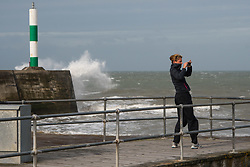 © Licensed to London News Pictures. 19/09/2018. Aberystwyth, UK. A woman photographs the stormy seas in Aberystwyth, as  Storm Ali, the first named storm of the UK winter season, gathers strength, promising very high winds and heavy rain for north western parts of the UK. Photo credit: Keith Morris/LNP