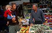"TV chef Jamie Oliver shops for produce with a favoured veg seller in Borough Market in Southwark, London. Oliver holds his box of fresh artichokes in one hand an his very young daughter Poppy on a Saturday morning. James ""Jamie"" Oliver, MBE (born 27 May 1975) is a British chef, restaurateur and media personality, known for his food-focused television shows, cookbooks and more recently his campaign against the use of processed foods in national schools. He strives to improve unhealthy diets and poor cooking habits in the United Kingdom and the United States."