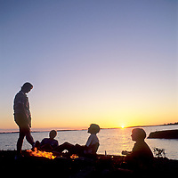A family relaxes around a campfire by Lake of the Woods, near Kenora, Ontario, Canada.
