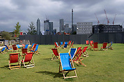 With the dark construction of more development at Nine Elms in the distance, vvacant red and blue deckchairs are randomly places on a grassy area at Battersea Power Station in south London, on 20th September 2021, in London, England.