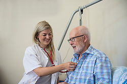 Female doctor with stethoscope listening the heartbeat of a senior man, Bavaria, Germany, Europe