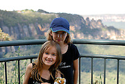 Two sisters (6 years old and 10 years old) posing in front of the Three Sisters rock formation. Katoomba, Blue Mountains, Australia