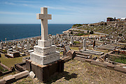 Cross memorial in front of graves. The Waverley Cemetery opened in 1877 and is a cemetery located on top of the cliffs at Bronte in the eastern suburbs of Sydney. It is noted for its largely intact Victorian and Edwardian monuments. The cemetery contains the graves of many significant Australians including and the poet Henry Lawson and Australia's first Prime Minister, Sir Edmund Barton, who is interred at South Head...Architecturally, Waverley Cemetery is significant in that it showcases examples of Stonemasonry and funerary art dating back from the 19th century,with features (such as the gates, buildings and fencing) that due to their intact nature are considered of outstanding aesthetic value...Poetically, the juxtaposition of the tombs and memorials overlooking the pacific ocean of the sea makes the cemetery a unique place.