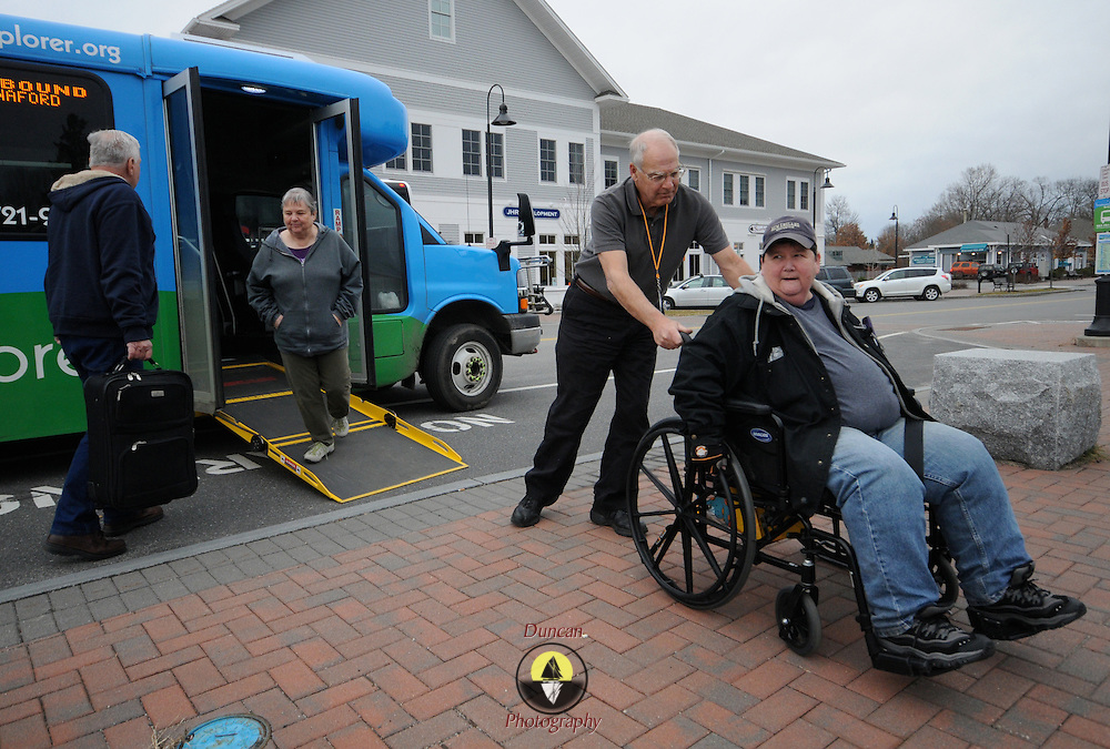 """11/17/11 -- BRUNSWICK, Maine. Driver Gregory Guckenburg, 62, assists Pam Boucher, 59, of Brunswick with getting off of the Brunswick Explorer.  """"If it wasn't for this bus we wouldn't get out to anywhere,"""" said Boucher. Boucher and her friend, Becky Estabrook, 58, in the door, who travels with her, were very positive about the bus, which seats as many as 15 people, including Boucher, who uses a wheelchair lock-in system. Photo by Roger S. Duncan."""