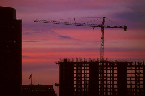 Stock photo of a silhouette of a crane and building frame against a sunset in Houston Texas.