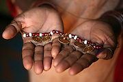 """Vimala Madar, 40, holds her """"muttu"""", the red and white beaded necklace tied around her neck during the dedication ceremony performed on her when she was ten years old to convert her into a Devadasi.  During this ceremony, Madar was """"married"""" to the Hindu deity, Yellamma, and was then considered one of Yellamma's servants.  From this day on, she was no longer eligible to marry a mortal and had to perform temple duties as well as fulfill the sexual needs of the priests and men in her community.  Madar's mother too was a Devadasi and tradition has it that any girl child of a Devadasi too must become a Devadasi, ensuring a constantly replenished supply of new young Devadasis."""
