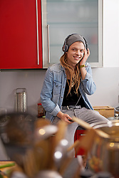 Young man with dreadlocks and piercing listening to music with headphones, Munich, Bavaria, Germany