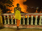 """24 APRIL 2014 - CHIANG SAEN, CHIANG RAI, THAILAND: A Buddhist novice watches a wildfire started on a nearby farm burn towards his temple in Chiang Rai province, Thailand. Farmers in Thailand and neighboring Laos and Myanmar still practice """"slash and burn"""" agriculture, burning out their fields in February, March and April before the start of the rainy season. The Thai government is trying to put a stop to the practice in Thailand but farmers continue to burn. Chiang Rai province in northern Thailand is facing a drought this year. The 2014 drought has been brought on by lower than normal dry season rains. At the same time, closing dams in Yunnan province of China has caused the level of the Mekong River to drop suddenly exposing rocks and sandbars in the normally navigable Mekong River. Changes in the Mekong's levels means commercial shipping can't progress past Chiang Saen. Dozens of ships are tied up in the port area along the city's waterfront.                   PHOTO BY JACK KURTZ"""