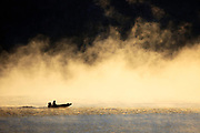 Boater in early morning fog at Gates of the Mountains area on the Missouri River, Montana.